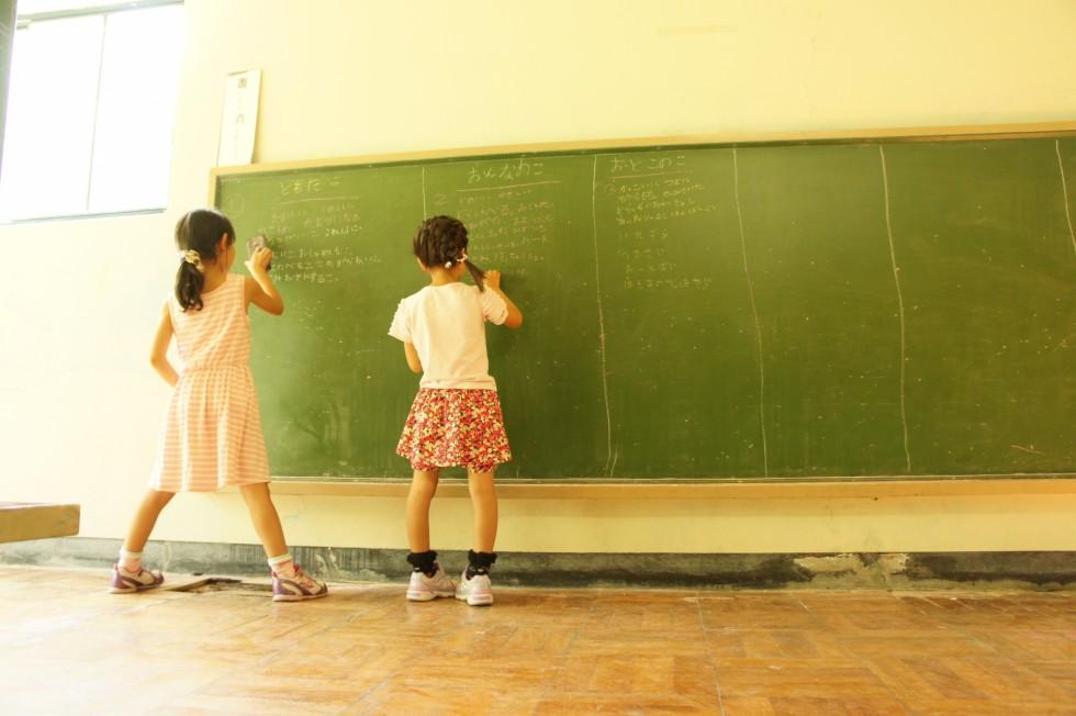 黒板に文字を書く子どもたちの画像です