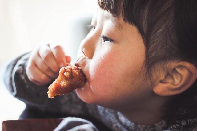 唐揚げを食べている子どもの画像