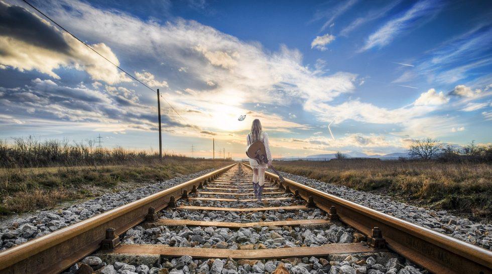 線路の上を太陽に向かって歩く女性