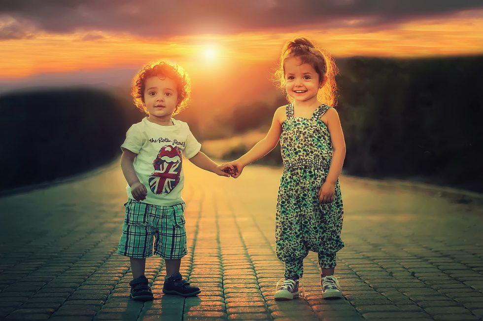 男の子と女の子が夕日をバックに手をつなぐ写真
